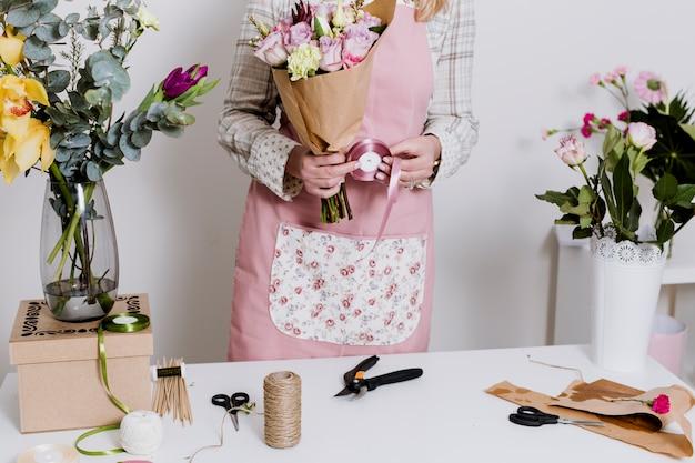 Upraw kwiaciarnia w fartuchu robi wiązce