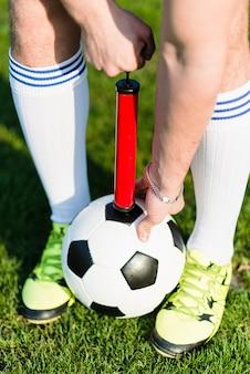 Upraw mężczyzna pompuje piłki nożnej