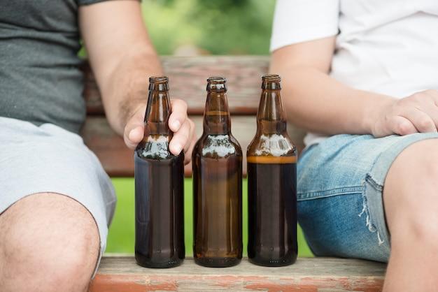 Upraw mężczyzna siedzi na ławce blisko piwa