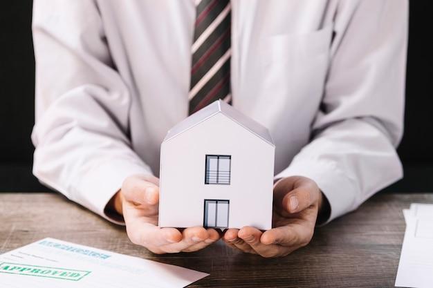 Upraw mężczyzna trzyma papierowego dom