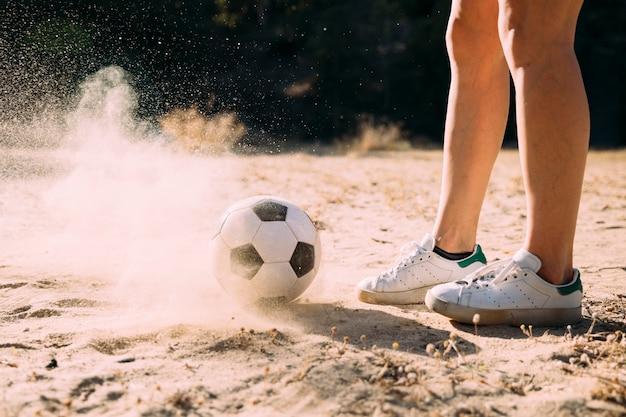 Upraw nogi sportowe stojące przy piłce nożnej na zewnątrz