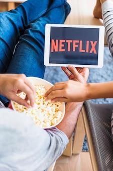 Upraw pary jedzenie popcorn podczas oglądania serii netflix w salonie