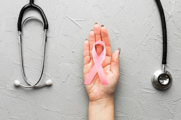 Upraw ręka z różowym tasiemkowym pobliskim stetoskopem