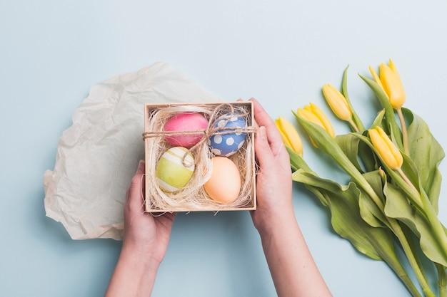 Upraw ręki trzyma jajka blisko tulipanów