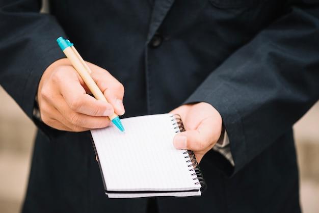 Uprawa człowieka pisania w pustym notesie