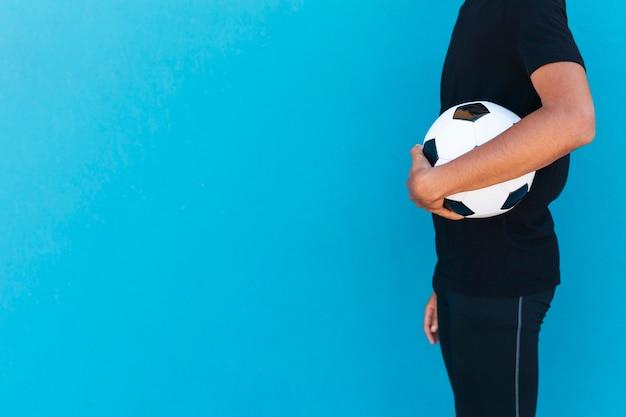 Uprawa człowieka stojącego z piłką nożną
