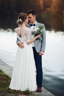 Uprawa eleganckich nowożeńców w pobliżu jeziora
