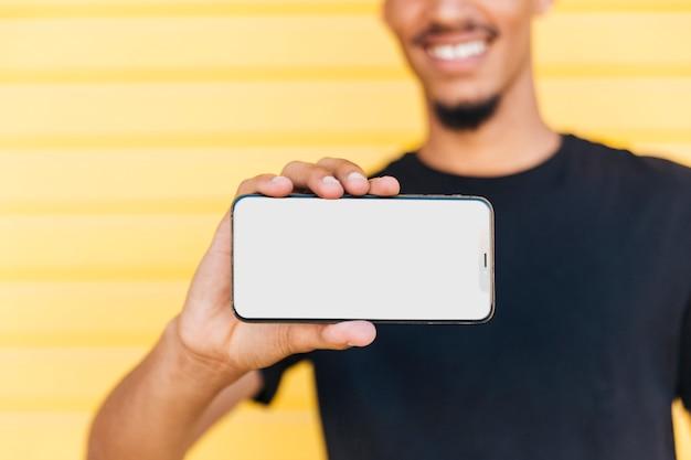 Uprawa etniczny mężczyzna pokazuje smartphone