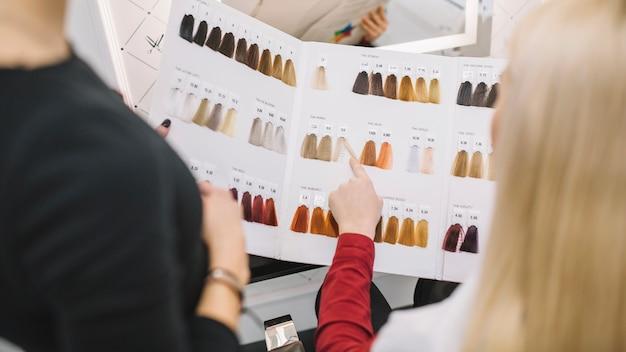 Uprawa klienta wybiera kolor włosów w salonie