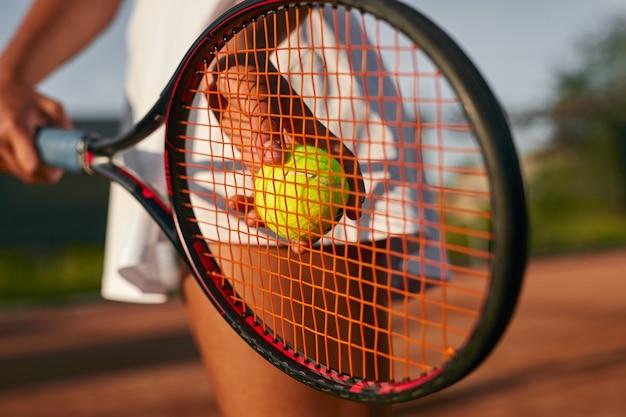 Uprawa kobiety, grając w tenisa na korcie