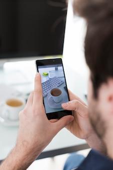 Uprawa mężczyzna bierze obrazek filiżanka w biurze