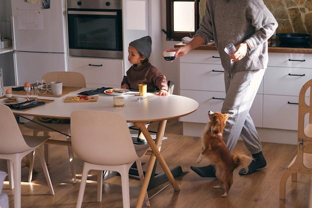 Uprawa matka z córeczką i rasowym psem podczas śniadania