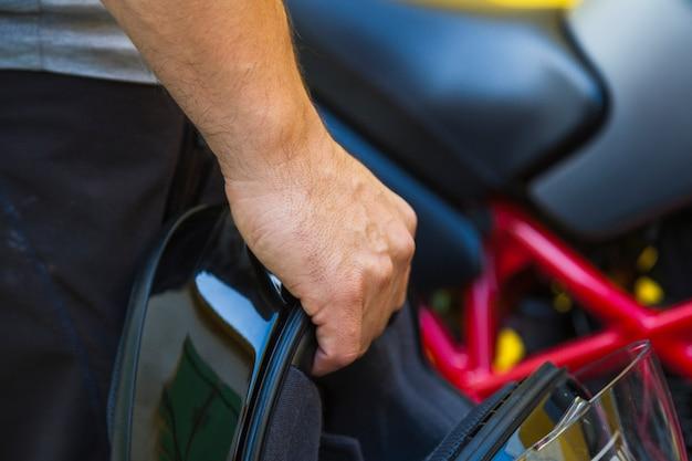 Uprawa mężczyzna trzyma motocyklu hełm