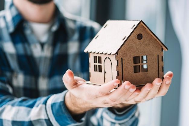 Uprawa mężczyzna trzyma zabawka dom