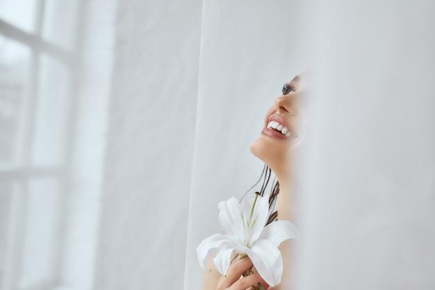 Uprawa młoda brunetka kobieta ze szczerym uśmiechem trzymając kwiat lilii w pobliżu okna