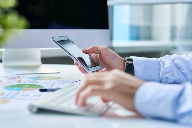Uprawa przedsiębiorcy ze smartfonem w miejscu pracy