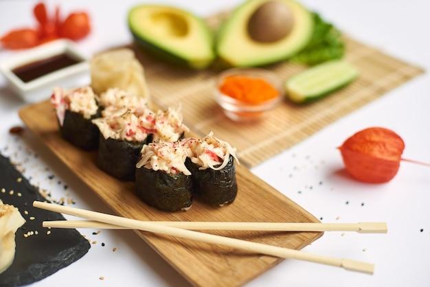 Uprawa smacznej rolki sushi zwieńczona posiekanymi paluszkami z owoców morza