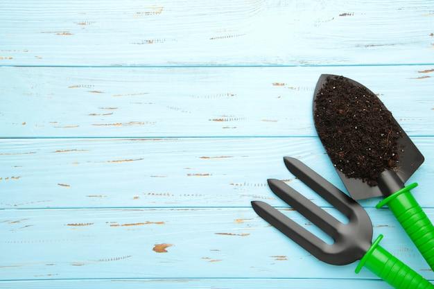 Uprawiać ogródek narzędzia na błękitnym drewnianym tle z ziemią