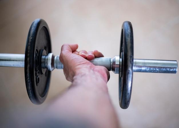 Uprawiaj sport w domu. wytnij widok dłoni trzymającej ciężar hantle