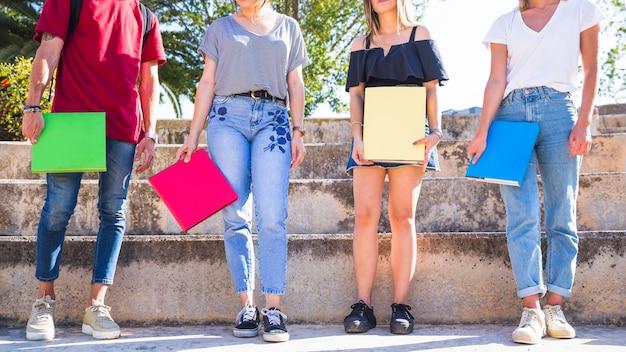 Uprawiaj uczniów z podręcznikami stojącymi na schodach