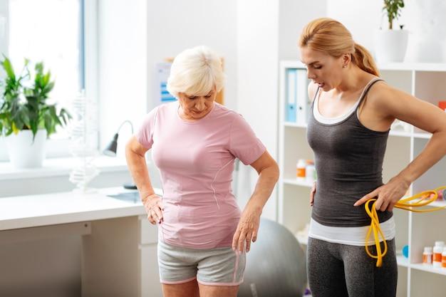 Uprawianie sportu. przystojna wysportowana kobieta trzymająca gumkę podczas rozmowy z pacjentem o nowych ćwiczeniach