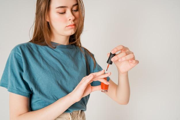 Uprawy fotografia młoda śliczna nastoletnia dziewczyna maluje gwoździe odizolowywających na szarość