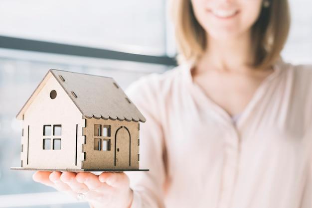 Uprawy kobieta demonstruje zabawka dom