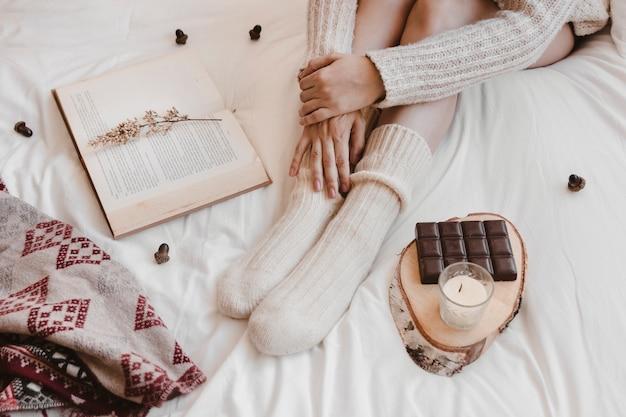 Uprawy kobiety obsiadanie między książką i czekoladą