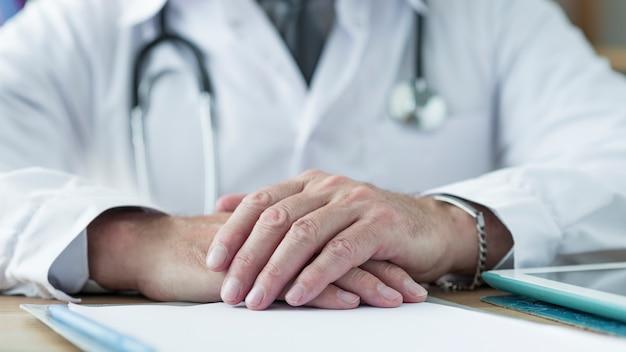 Uprawy lekarki mienia ręki na biurku