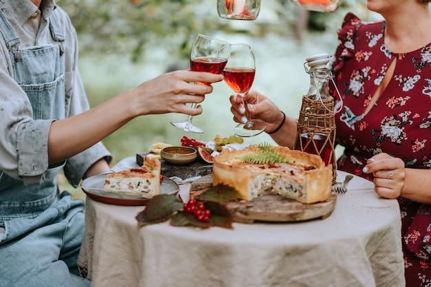Uprawy para z szkłami przy obiadowym stołem w jesieni plenerowej