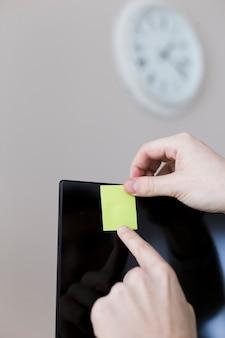 Uprawy ręce wiszące notatki na monitorze