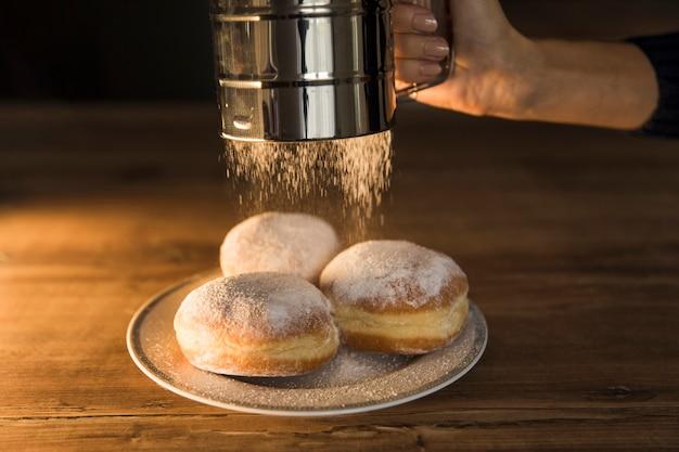 Uprawy ręka rozlewa sproszkowanego cukier na donuts
