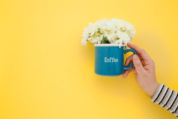 Uprawy ręka trzyma kubek z kwiatami