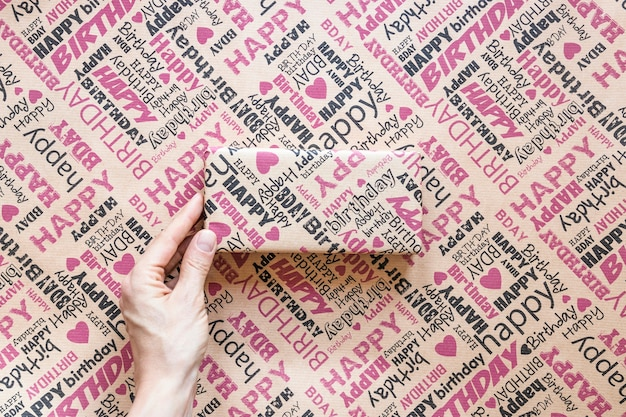 Uprawy ręki mienia prezent nad opakunkowym papierem