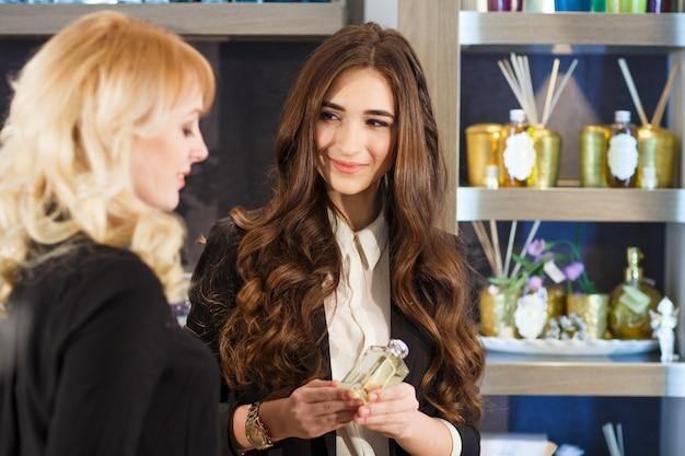 Uprzejma konsultantka pomaga klientowi w wyborze sklepu z kosmetykami.