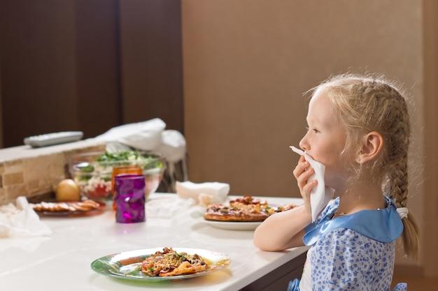 Uprzejma mała dziewczynka je domową pizzę?