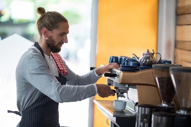 Uprzejmy kelner robi filiżankę kawy