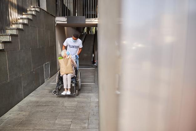 Uprzejmy opiekun wymieniający spojrzenia ze starszą kobietą na wózku inwalidzkim z torbą na zakupy