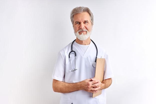 Uprzejmy przyjazny kaukaski starszy mężczyzna lekarz w mundurze stojaka patrząc na kamery, pozowanie. szary