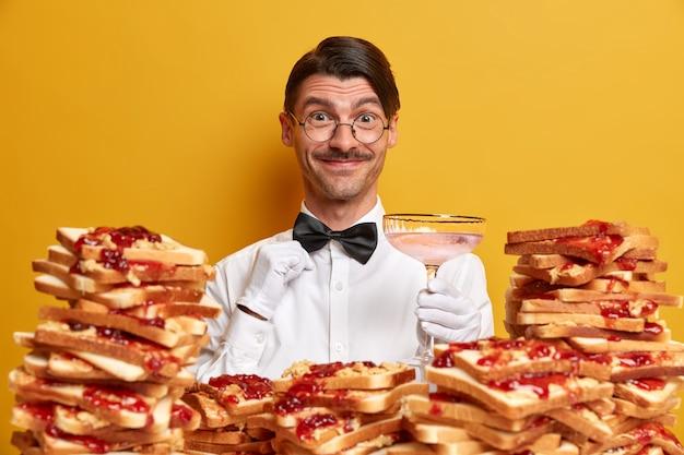 Uprzejmy, wesoły kelner w mundurze, trzyma kieliszek, prezentuje nowy trunek odwiedzającym restaurację, ma fryzurę i wąsy, stoi przy stosie pysznych kanapek pod dachem