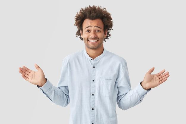 Ups, to moja wina! wahający się, wesoły, ciemnoskóry mężczyzna ma zdziwiony wyraz twarzy, wzrusza ramionami, pozytywny uśmiech, żałuje, że zapomina pogratulować przyjacielowi urodzin, odizolowany na białej ścianie