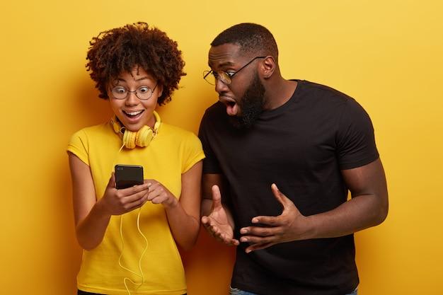 Uradowana afro kobieta wpatruje się w urządzenie smartphone podłączone do słuchawek