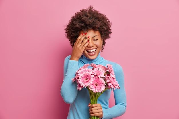 Uradowana afroamerykanka głośno się śmieje, trzyma dłoń na twarzy, stoi w pomieszczeniu z bukietem kwiatów gerbera