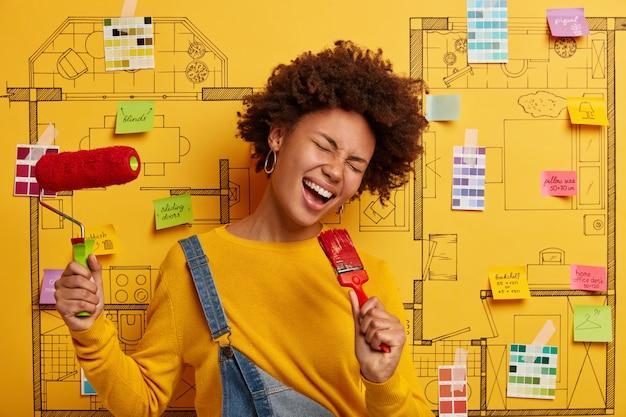 Uradowana afroamerykanka trzyma pędzel jako mikrofon, dobrze się bawi po malowaniu, nosi żółty sweter, pozuje przeciwko projektowi domu, zajęta naprawą mieszkania, przechyla głowę i się śmieje