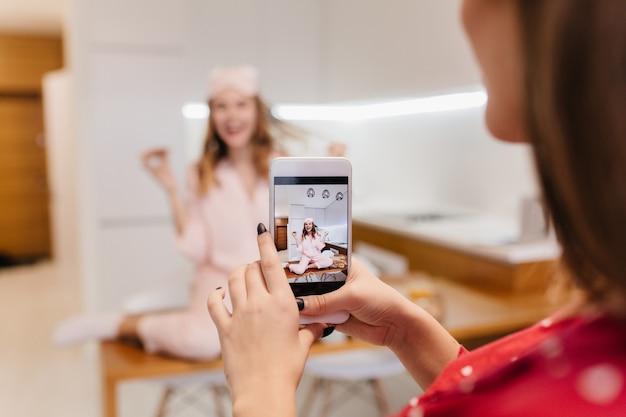 Uradowana biała dziewczyna je pizzę i bawi się włosami. brunetka dama trzyma smartfon i robi zdjęcie przyjaciela w kuchni z jasnym wnętrzem.
