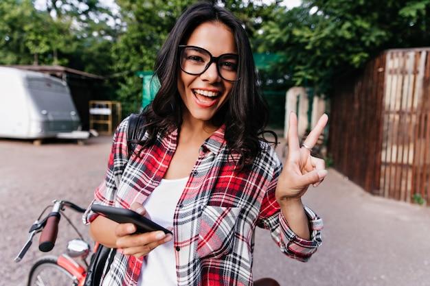 Uradowana biała dziewczyna w okularach wyrażająca pozytywne emocje podczas relaksu w mieście. zewnątrz zdjęcie czarującej kobiety w kraciastej koszuli, trzymając smartfon.