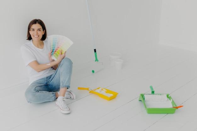Uradowana brunetki kobieta pokazuje próbki kolorów