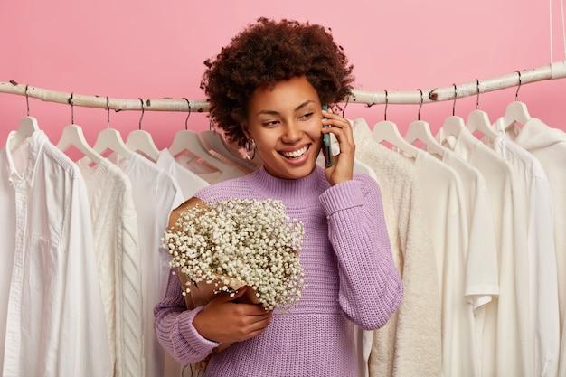 Uradowana ciemnoskóra dama trzyma telefon komórkowy, stoi z bukietem w pobliżu stojaka pełnego ubrań, ubrana w fioletowy sweter z dzianiny, odizolowany na różowym tle.