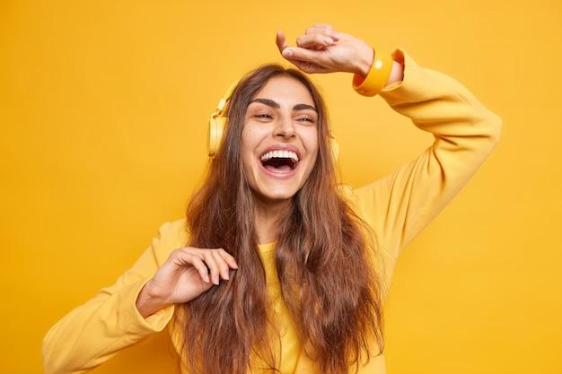 Uradowana ciemnowłosa kobieta czuje się bardzo szczęśliwa tańcząc z rytmem muzyki dreszcze w pomieszczeniu, podczas gdy słuchanie listy odtwarzania przez słuchawki ma optymistyczny nastrój na białym tle nad żółtą ścianą.
