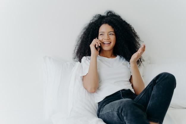 Uradowana, etniczna dama z kręconymi włosami rozmawia przez telefon, gestykuluje i śmieje się z radości, wygląda gdzieś na boku